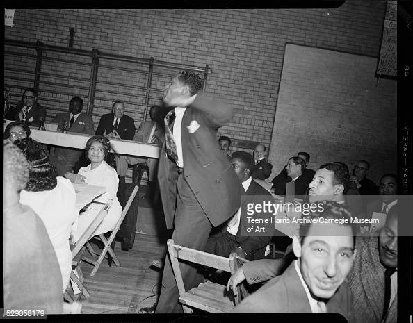 Man standing and gesturing in front of Atty Paul F Jones boxer Ezzard Charles James S Devlin and baseball player Luke Easter seated behind banquet...