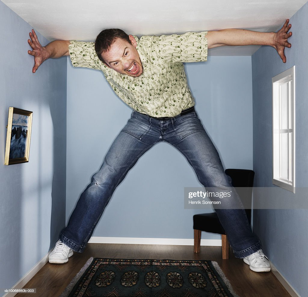 Man standing and screaming in small living room, portrait : Stock Photo