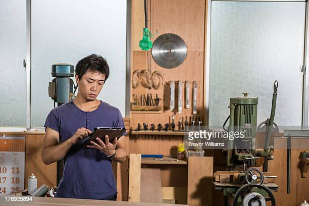 A man standing and using a tablet in a workshop