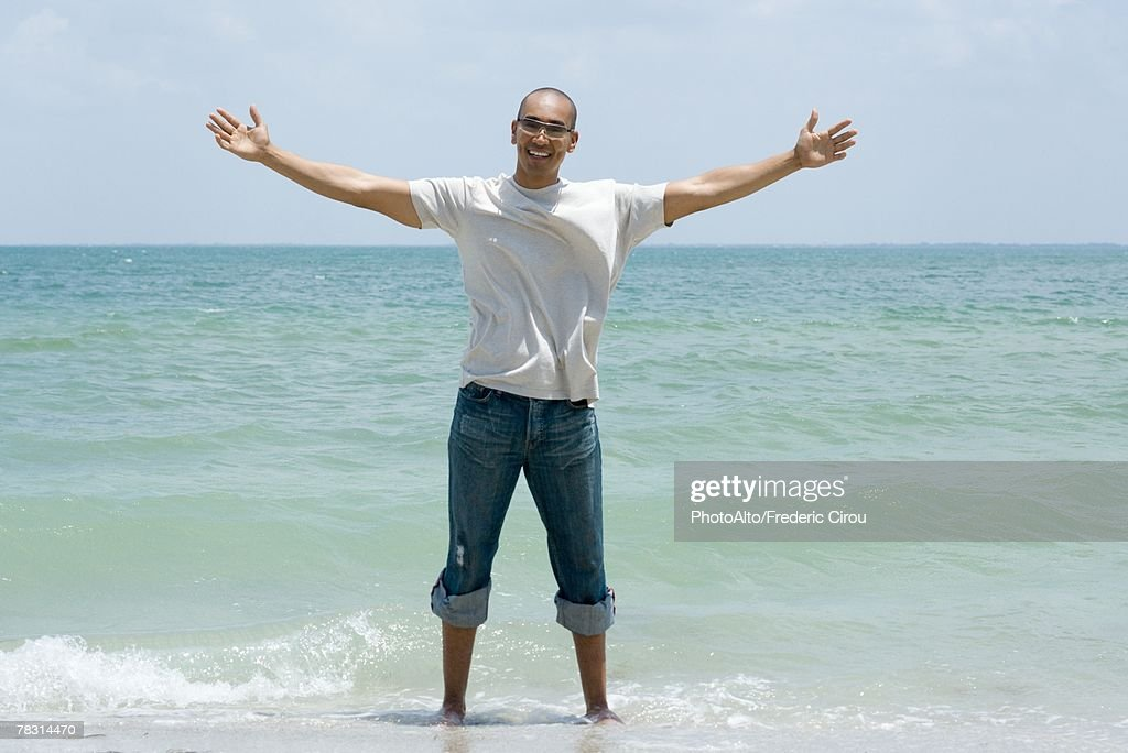 Man standing ankle deep in ocean with arms outstretched, smiling at camera