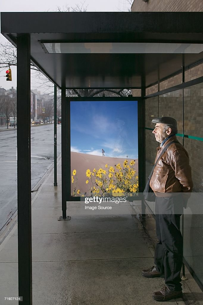 Man standing at bus shelter : Stock Photo