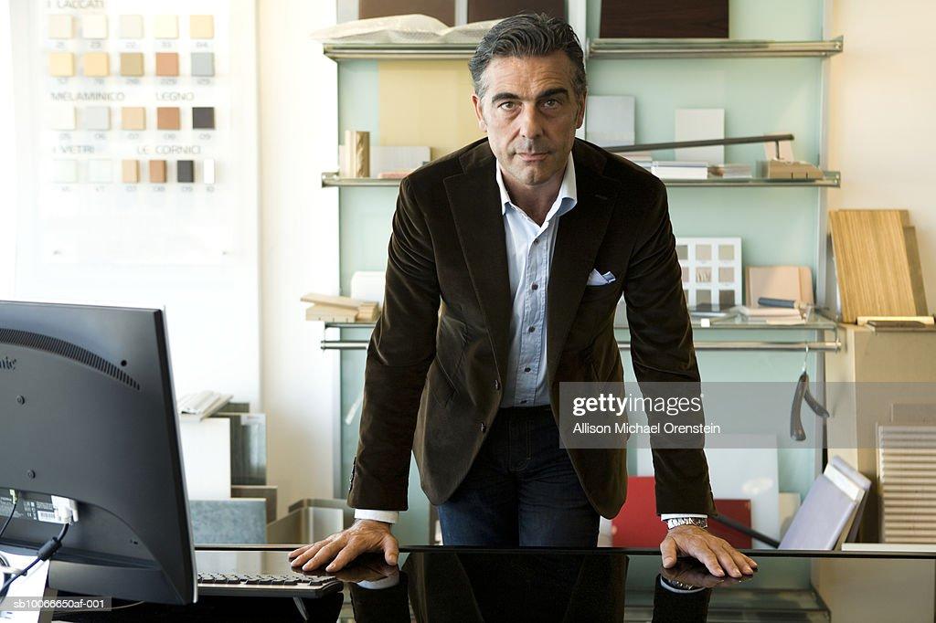 Man standing at desk in office, portrait