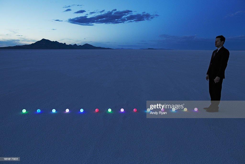 Man standing at line of glowing orbs in desert