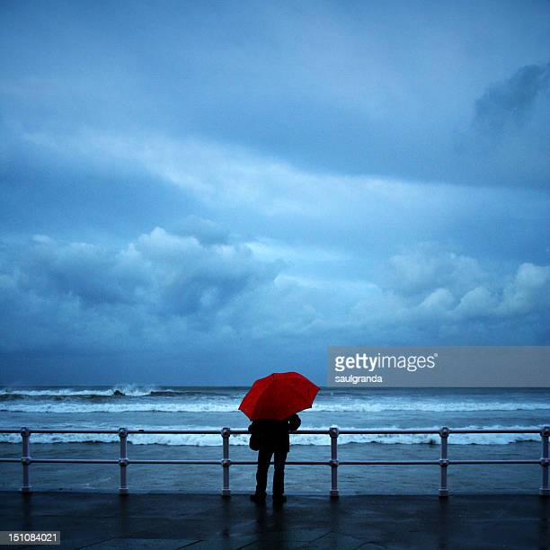 Man standing at railing with umbrella