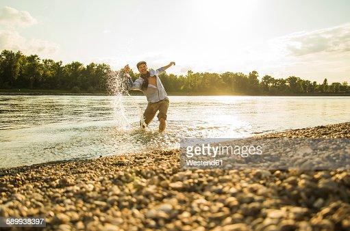 Man standing at riverside splashing with water