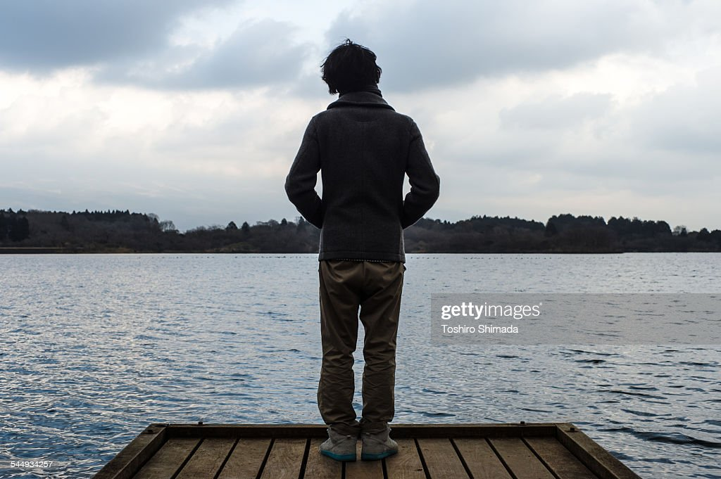 A man standing at the edge of a dock