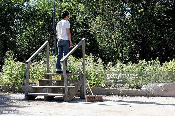 A man standing at the top of a staircase going nowhere, rear view, outdoors