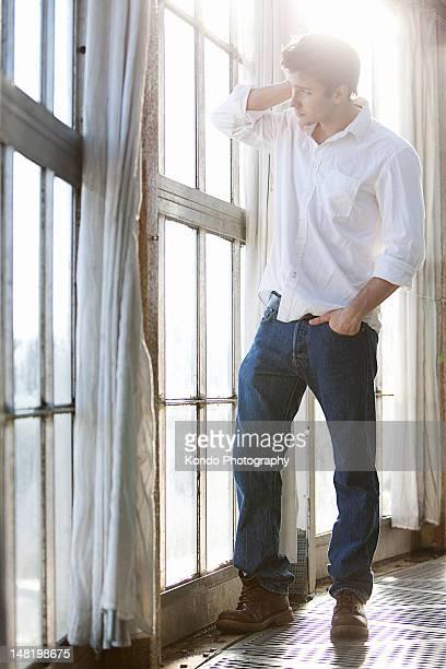Mann stehend am Fenster
