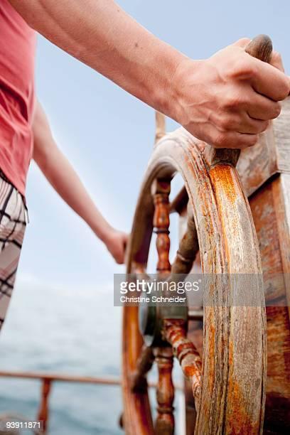 Man standing at wooden steering wheel
