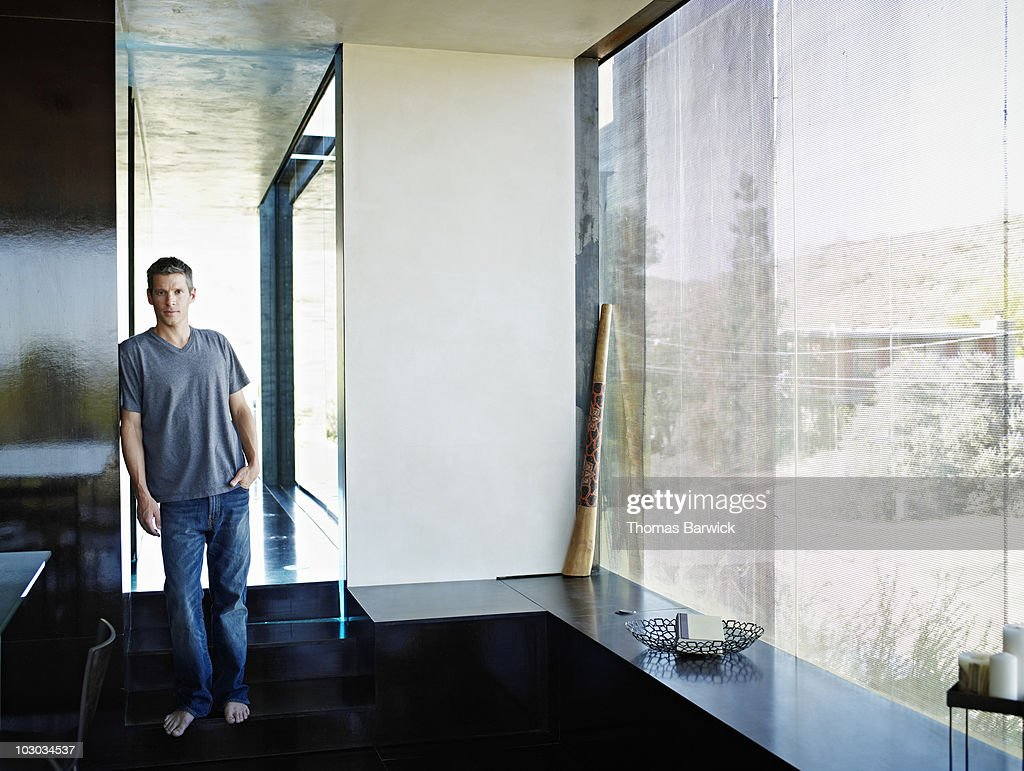 Man standing barefoot in hallway of home : Stock Photo