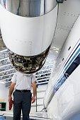 Man standing behind airplane engine in hangar