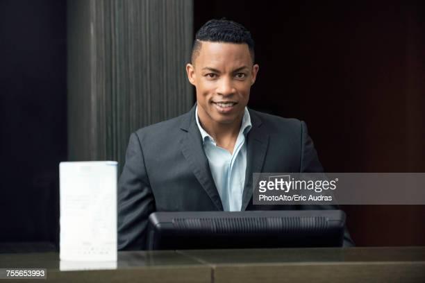 Man standing behind bank teller counter, portrait