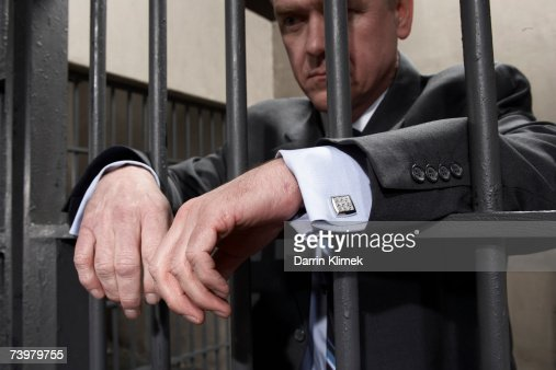 Man standing behind bars in prison cell, close-up of hands : Stock Photo