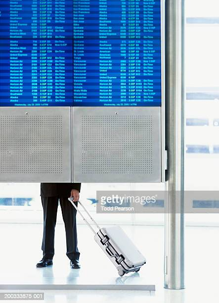 Man standing behind flight schedule board