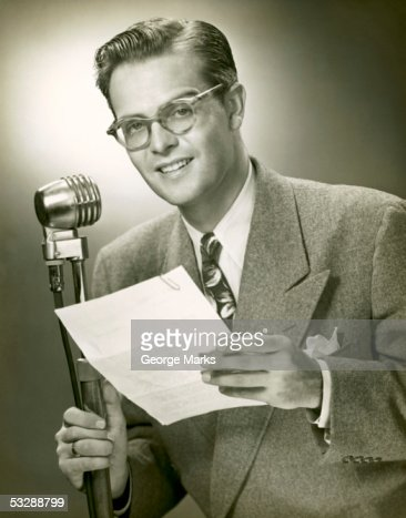Man standing behind microphone : Stock Photo