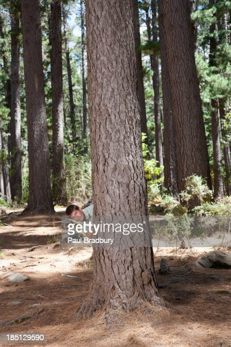 Man standing behind tree