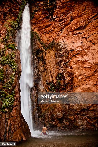 Man standing below waterfall