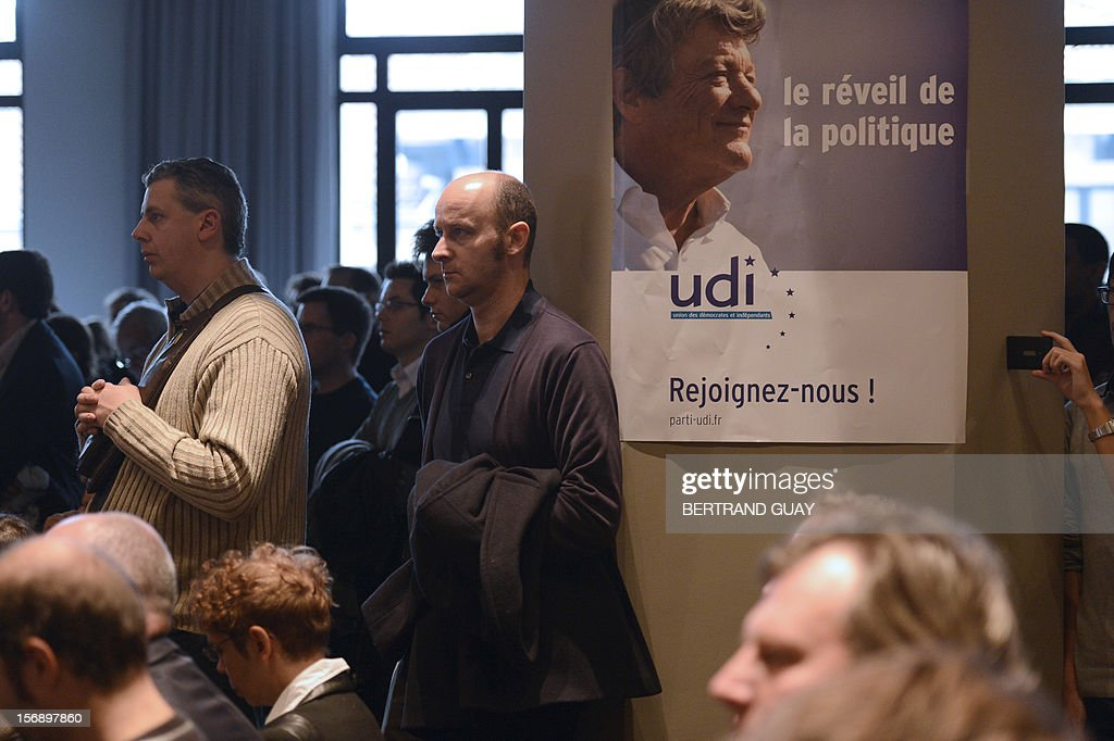 A man standing beside a poster showing head of Union of Democrats and Independents (UDI) party, Jean-Louis Borloo attends a meeting with new UDI members on November 24, 2012 at the 'Maison de la Mutualite' conference centre in Paris. France's centre-right UDI and far-right Front National (FN) recently declared registering an increasing number of new memberships since the bitterly contested leadership election of main opposition right-wing party Union for a Popular Movement (UMP).