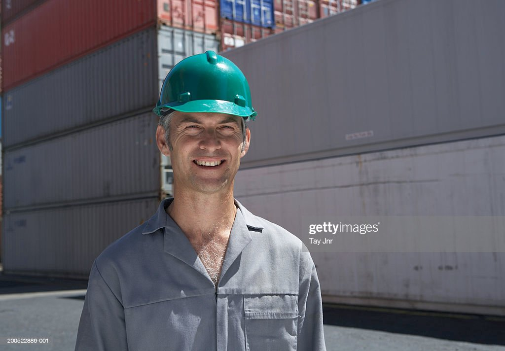 Man standing beside cargo containers, wearing hard hat, smiling : Stock Photo