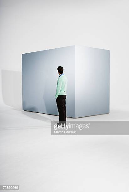 Man standing beside empty giant box