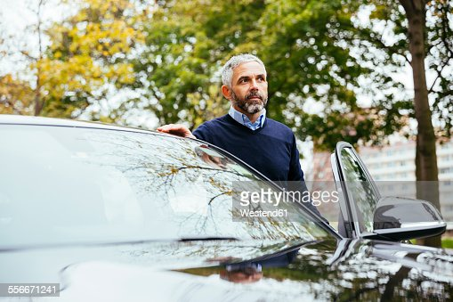 Man standing beside his car
