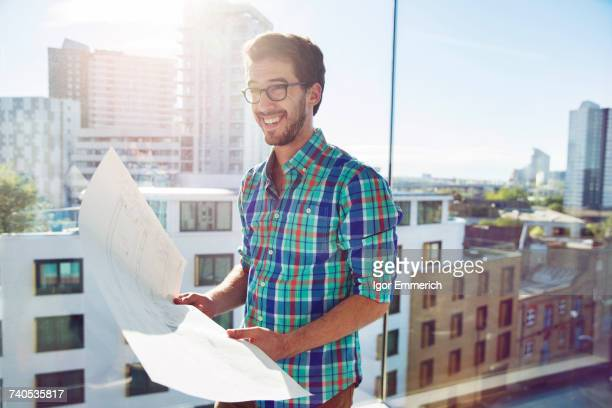 Man, standing beside office window, looking at plans, smiling