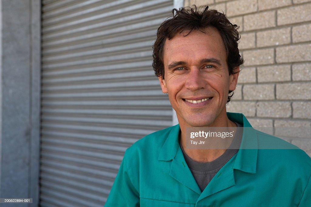 Man standing beside roller door, smiling, close-up, portrait : Stock Photo