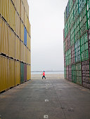 Man standing between containers in a shipping yard