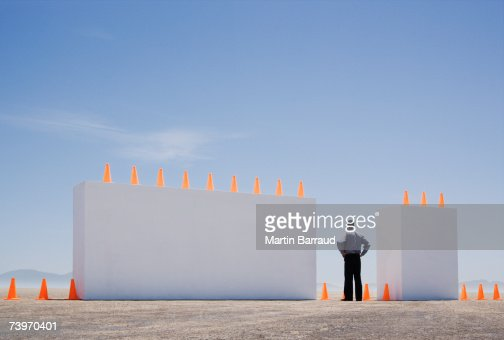 Man standing between two monolithic barriers lined with safety cones : Stock Photo