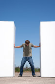 Man standing between two walls outdoors pushing