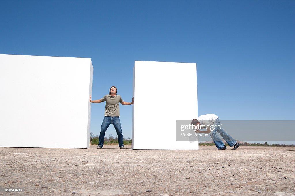 Homem de pé entre duas paredes de empurrar ao ar livre com Adversário : Foto de stock