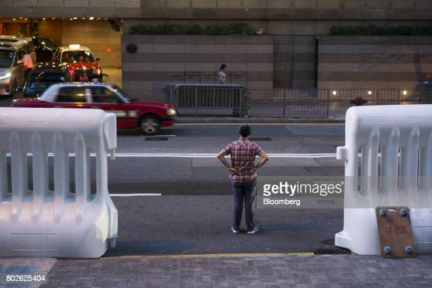 A man standing between water barricades waits to cross a road near the Hong Kong Convention and Exhibition Center ahead of Chinese President Xi...