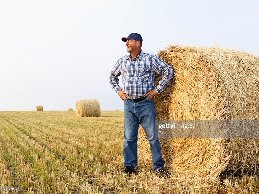 Man Standing by Bale of Hay