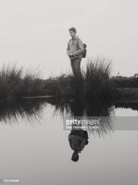 Man Standing By Calm Lake Against Clear Sky
