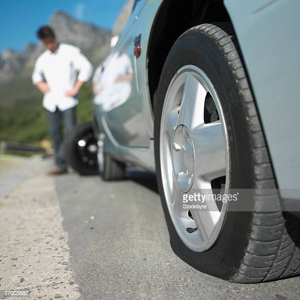 Man standing by car with flat tire, focus on tire