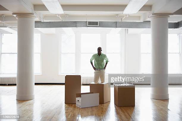 Man standing by cardboard boxes in empty office
