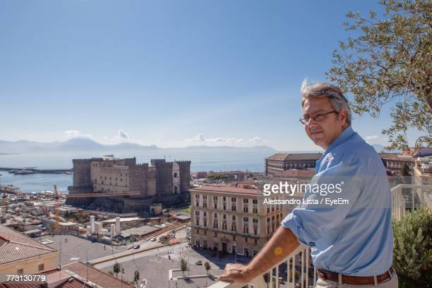 Man Standing By Cityscape Against Blue Sky