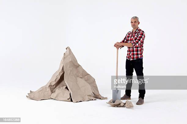 A man standing by dug up construction paper rock, next to an artificial paper boulder