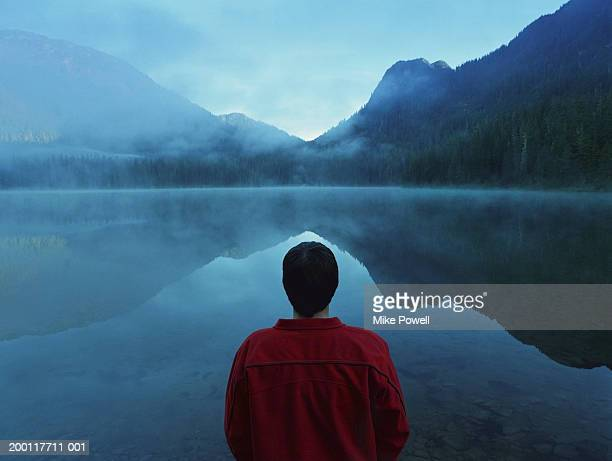 Man standing by lake covered with fog, rear view