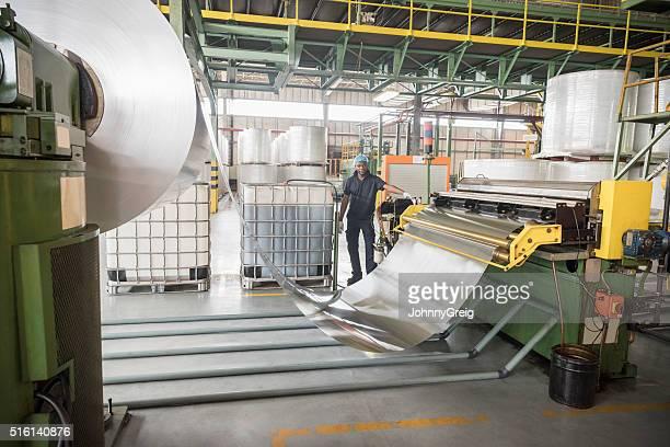 Mann stehend durch große Rollen aus aus Aluminium in Fabrik
