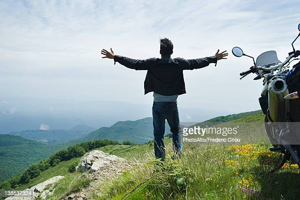 Man standing by motorcycle on top of mountain, arms outstretched