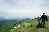 Man standing by motorcycle on top of mountain, rear view