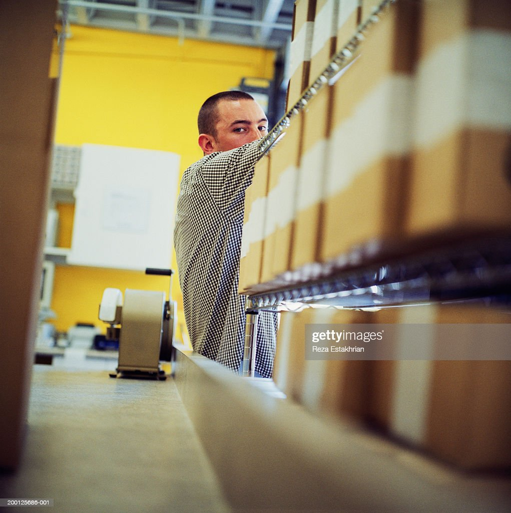 Man standing by racks of boxes in mailing room : Stock Photo