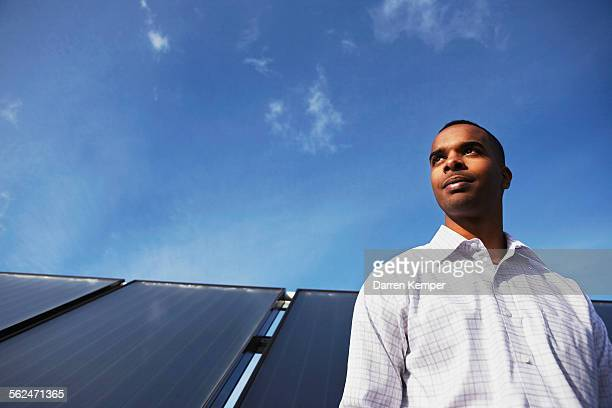 Man standing by solar panel