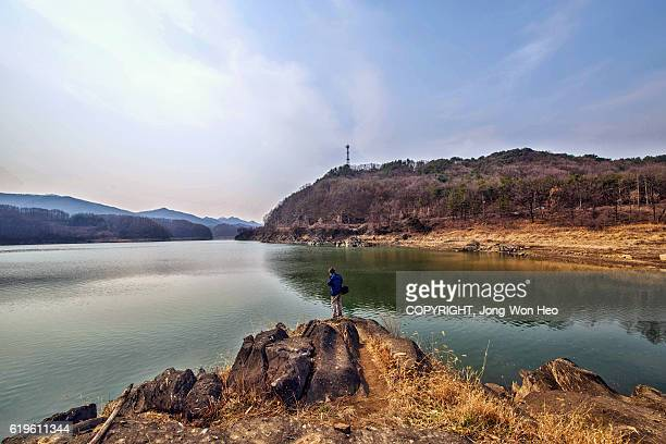 A man standing by the lake