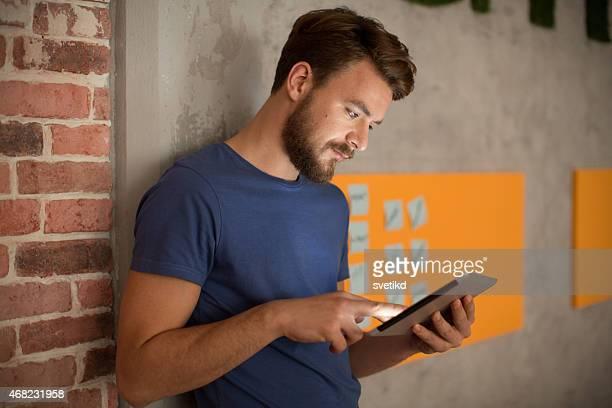 HOMME DEBOUT par mur et à l'aide de tablette numérique.