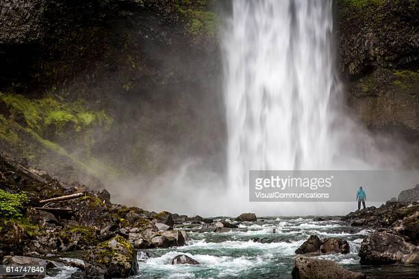 Man standing close to huge waterfall.
