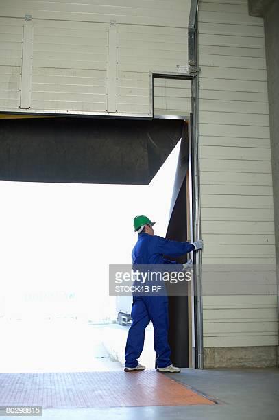 Man standing handling a roller shutter