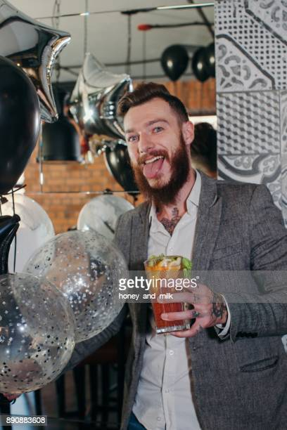 Man standing in a bar with a cocktail sticking out his tongue