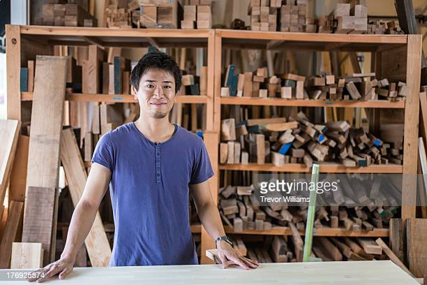 A man standing in a carpentry workshop
